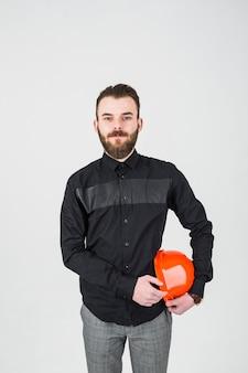 Ritratto di giovane ingegnere maschio sicuro contro il contesto bianco