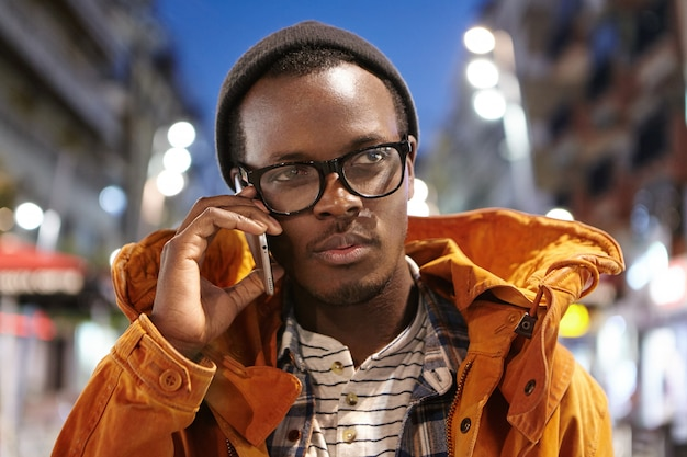 Ritratto di giovane maschio afroamericano alla moda che ha conversazione piacevole sul cellulare, trascorrendo la sera all'aperto con le luci della città