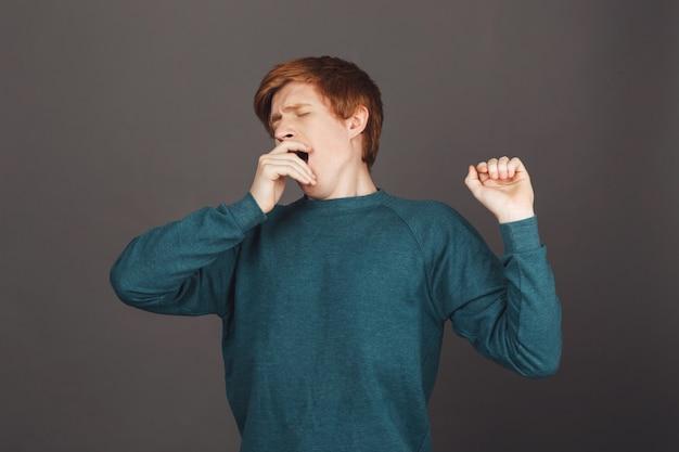 Ritratto di giovane maschio dai capelli rossi con i capelli corti in bocca fodera felpa verde con la mano