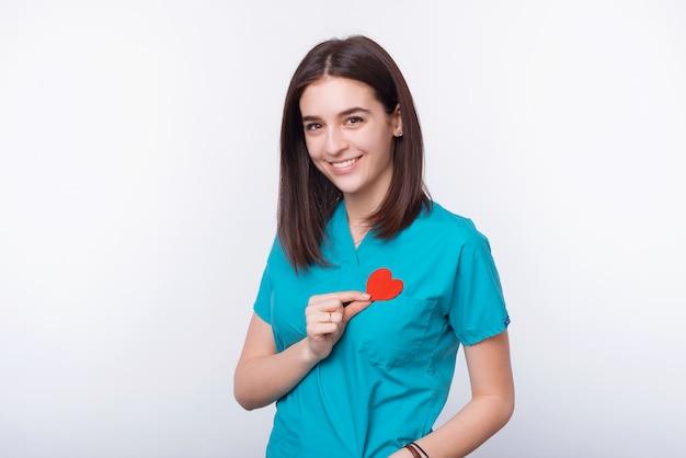 Ritratto di giovane medico allegro che tiene cuore di carta rosso sopra il petto
