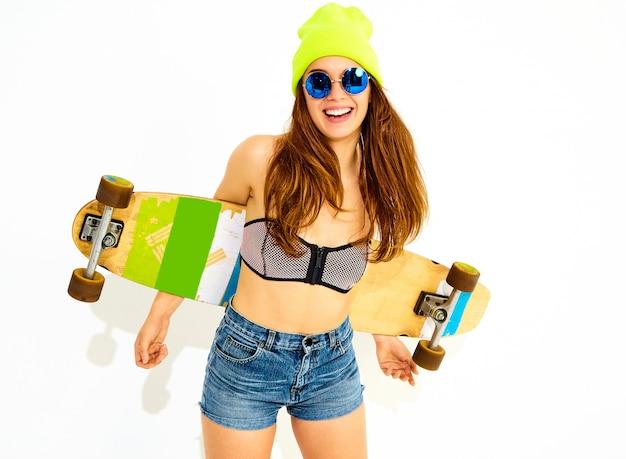 Ritratto di giovane modello di donna sorridente alla moda in costumi da bagno casual estate e berretto giallo in posa con scrivania longboard. isolato su bianco