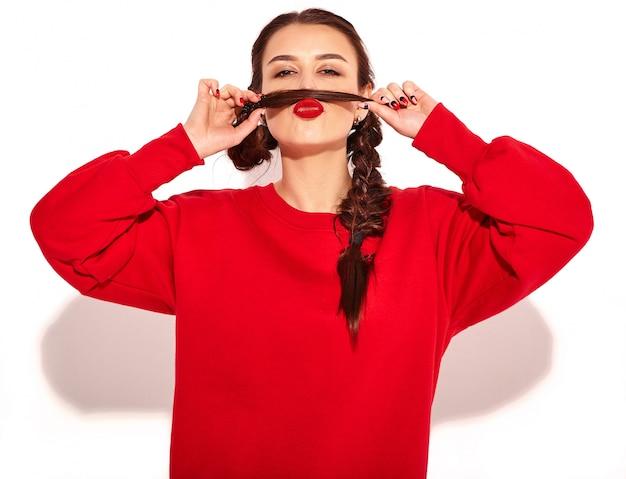 Ritratto di giovane modello di donna sorridente felice con trucco luminoso e labbra colorate con due trecce e occhiali da sole in abiti rossi estate isolati. fare baffi finti usando i propri capelli