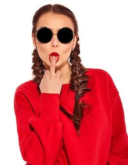 Ritratto di giovane modello di donna sorridente felice con trucco luminoso e labbra colorate con due trecce e occhiali da sole in abiti rossi estate isolati. leccare il dito medio, fanculo segno