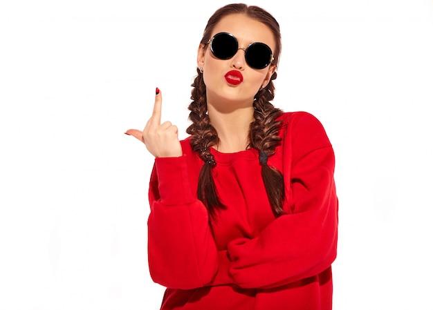 Ritratto di giovane modello di donna sorridente felice con trucco luminoso e labbra colorate con due trecce e occhiali da sole in abiti rossi estate isolati. mostrando il segno del cazzo