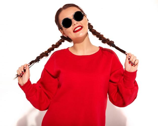 Ritratto di giovane modello di donna sorridente felice con trucco luminoso e labbra colorate con due trecce e occhiali da sole in abiti rossi estate isolati.