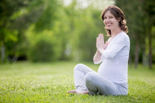 Ritratto di giovane modello incinta meditando sul prato erboso
