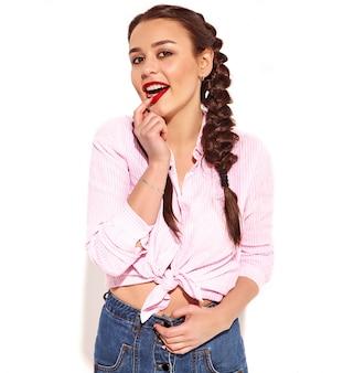 Ritratto di giovane modello sorridente felice della donna con trucco luminoso e labbra rosse con due trecce in camicia legata rosa variopinta di estate, isolata