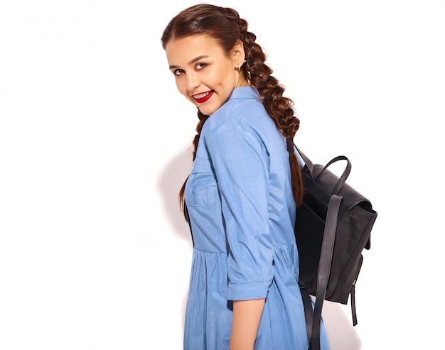 Ritratto di giovane modello sorridente felice della donna con trucco luminoso e labbra rosse con due trecce in mani in vestito blu variopinto da estate e zaino isolati.