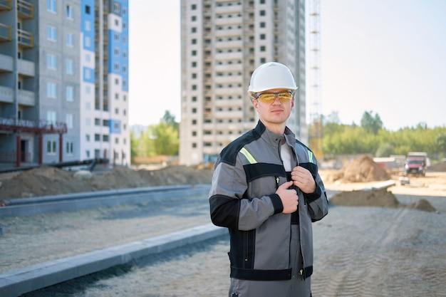 Ritratto di giovane operaio serio bello che indossa casco protettivo bianco e tuta da lavoro grigia