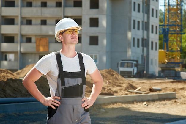 Ritratto di giovane operaio serio bello che indossa casco protettivo bianco, occhiali arancioni e tuta da lavoro grigia
