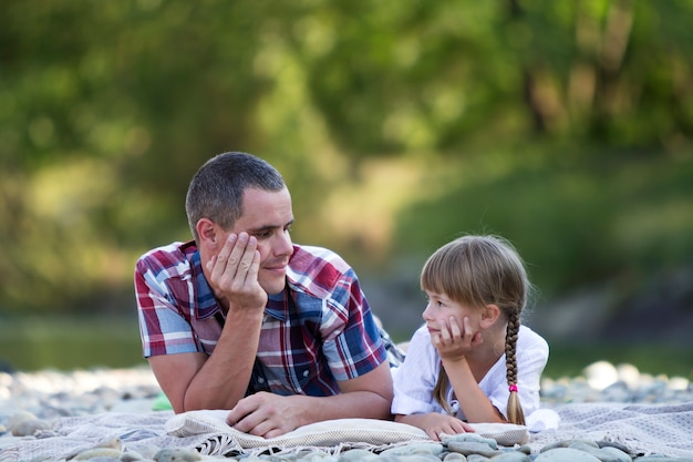 Ritratto di giovane padre e ragazza bionda sveglia con le trecce lunghe che mettono su sponda del fiume pebbled il giorno di estate luminoso sul bokeh verde vago degli alberi. amore, cura e perfetto concetto di vacanza.
