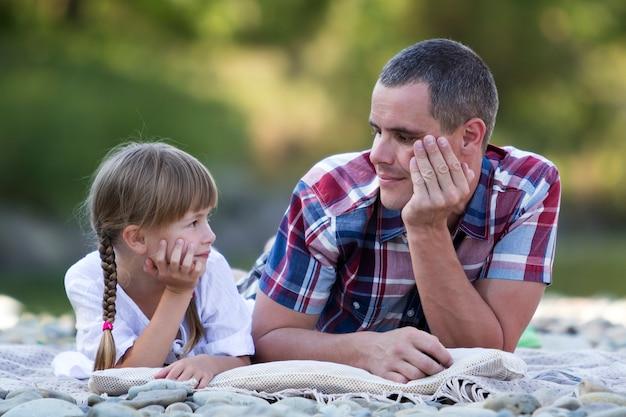 Ritratto di giovane padre e ragazza bionda sveglia con le trecce lunghe che pongono sulla sponda del fiume pebbled il giorno di estate luminoso sugli alberi verdi vaghi. amore, cura e perfetto concetto di vacanza.
