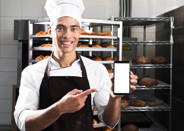 Ritratto di giovane panettiere maschio sorridente che mostra telefono cellulare davanti agli scaffali al forno del croissant