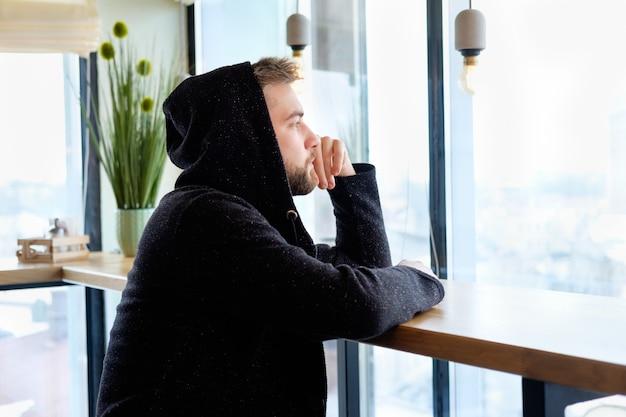 Ritratto di giovane pensieroso barbuto bell'uomo seduto nella caffetteria vicino alla finestra e guardando lontano