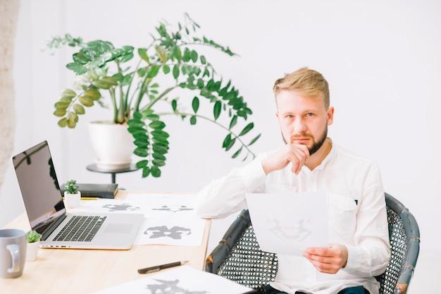 Ritratto di giovane psicologo maschio che tiene la carta in esame del inkblot del rorschach a disposizione che esamina macchina fotografica