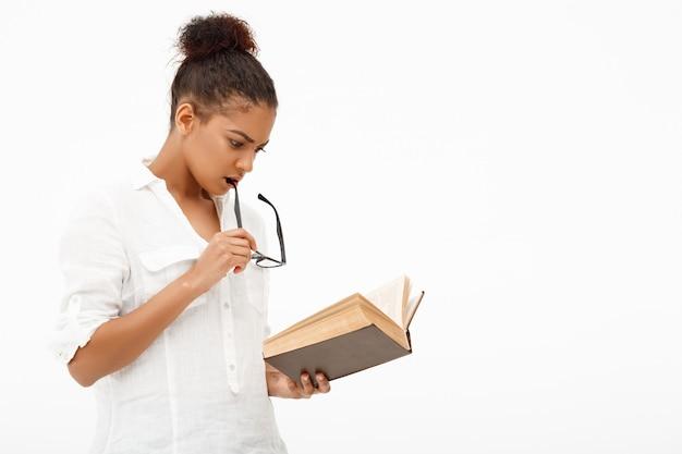 Ritratto di giovane ragazza africana con il libro sul muro bianco
