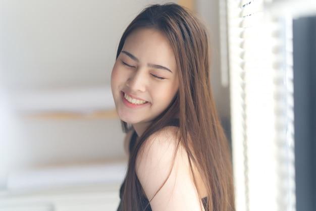 Ritratto di giovane ragazza asiatica carina chiudendo gli occhi con il sorriso in piedi accanto alla finestra