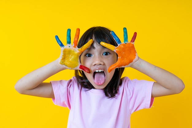 Ritratto di giovane ragazza asiatica con arte, colore di acqua divertente tailandese di manifestazione del bambino sulla palma e creatività del concetto dei bambini
