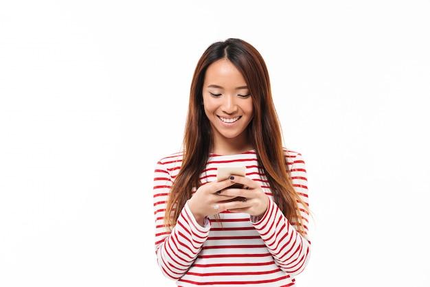 Ritratto di giovane ragazza asiatica sorridente che per mezzo del telefono cellulare