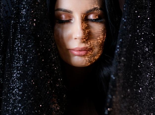 Ritratto di giovane ragazza attraente con tenero trucco e ombra sul viso circondato da pizzo glitter nero