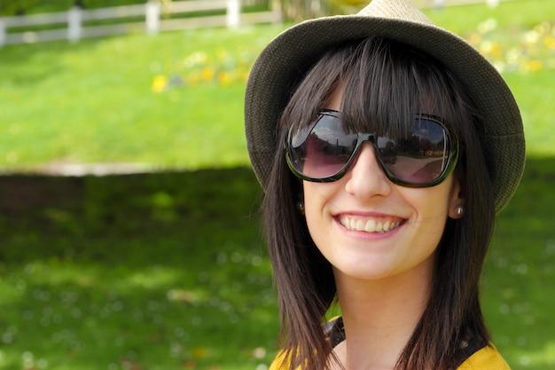 Ritratto di giovane ragazza bruna con cappello estivo nel parco