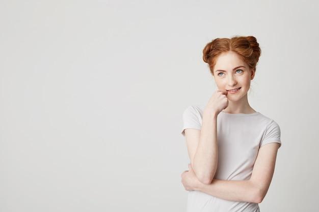 Ritratto di giovane ragazza carina sognante con i capelli rossi pensando di sognare toccando il mento.