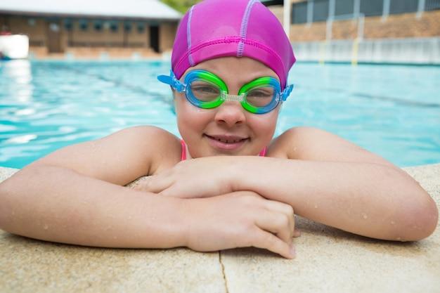 Ritratto di giovane ragazza che indossa occhiali da nuoto in piscina