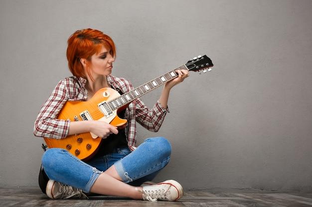 Ritratto di giovane ragazza con la chitarra su sfondo grigio.