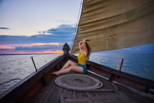 Ritratto di giovane ragazza esile sul tramonto nel mare. la giovane donna incontra l'alba sulla barca