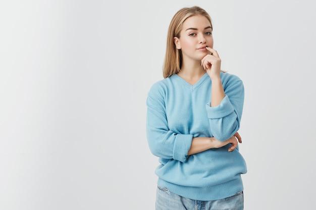 Ritratto di giovane ragazza europea bionda con pelle sana che indossa maglione blu e jeans che guardano con espressione calma e premurosa, riflettendo sulla preposizione che le è stata data.