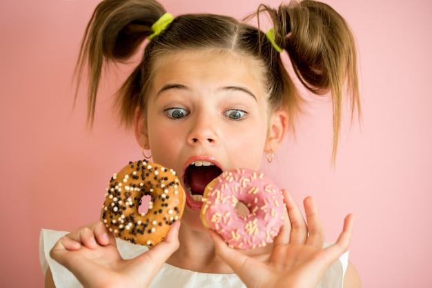 Ritratto di giovane ragazza guardando attraverso due ciambelle rosa