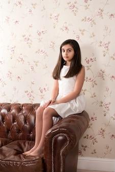 Ritratto di giovane ragazza in cima al divano