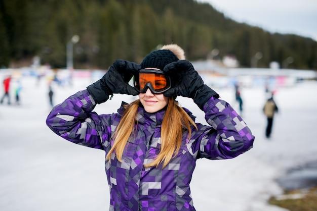 Ritratto di giovane ragazza sorridente che indossa i vetri dello sci nella stazione sciistica.