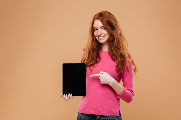 Ritratto di giovane ragazza sorridente di redhead che indica barretta alla compressa digitale