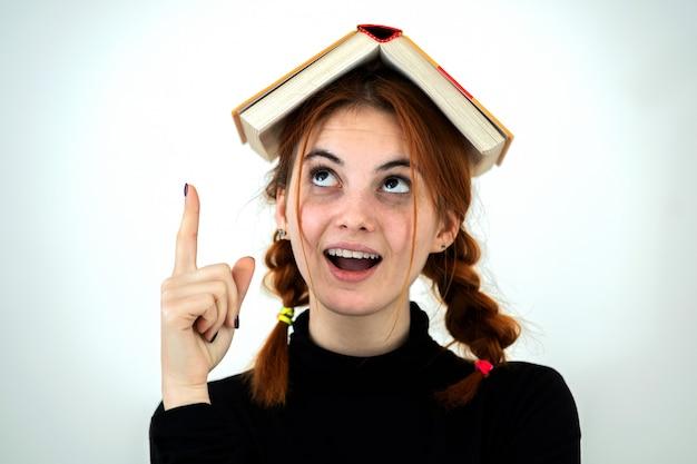 Ritratto di giovane ragazza sorridente divertente dello studente con un libro aperto sulla sua testa che tiene il suo dito del punto su che ha un'idea