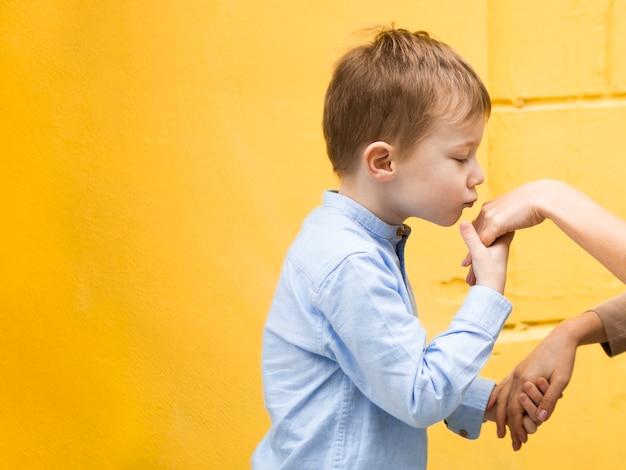 Ritratto di giovane ragazzo adorabile che bacia la sua mano delle madri