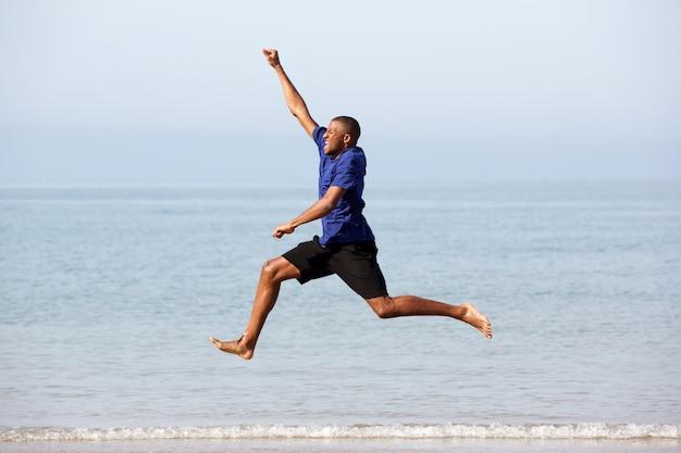 Ritratto di giovane ragazzo africano eccitato, correre e saltare lungo il mare