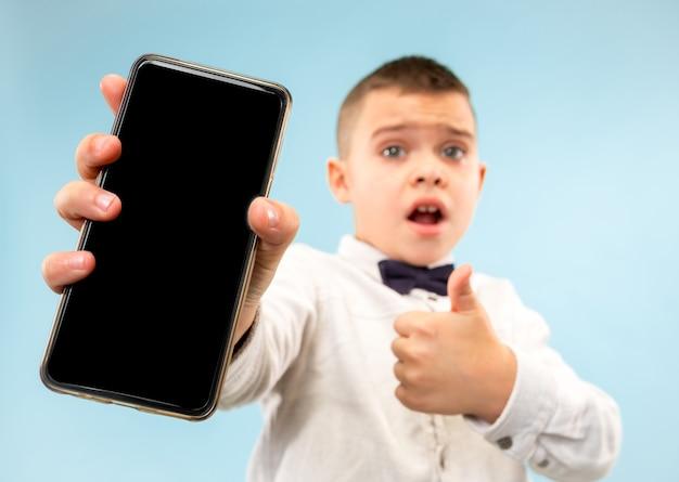 Ritratto di giovane ragazzo attraente che tiene smartphone in bianco