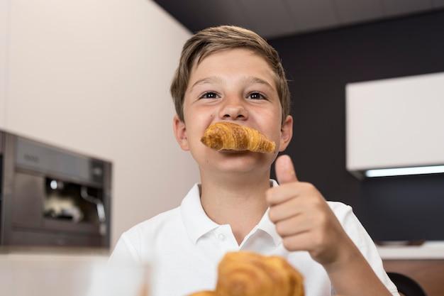Ritratto di giovane ragazzo che mangia i croissant