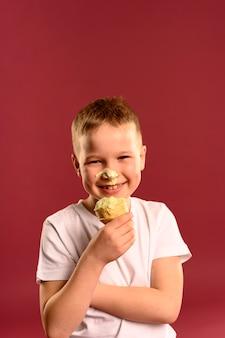 Ritratto di giovane ragazzo felice che mangia il gelato