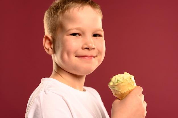 Ritratto di giovane ragazzo felice di mangiare il gelato