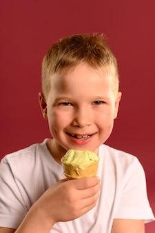 Ritratto di giovane ragazzo sveglio che mangia il gelato
