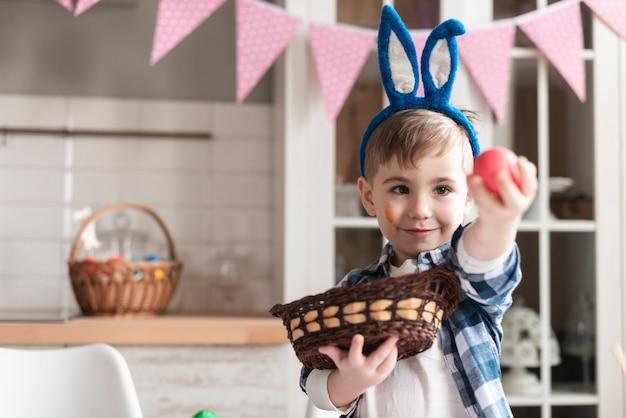 Ritratto di giovane ragazzo sveglio che tiene un uovo di pasqua
