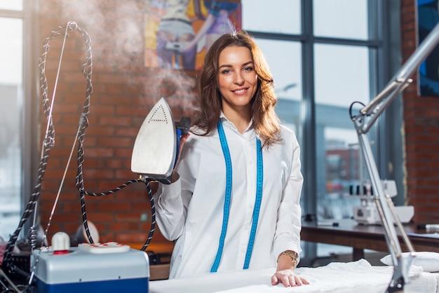 Ritratto di giovane sarto da donna castana caucasico attraente che sta in vestiti bianchi che tengono il ferro a vapore