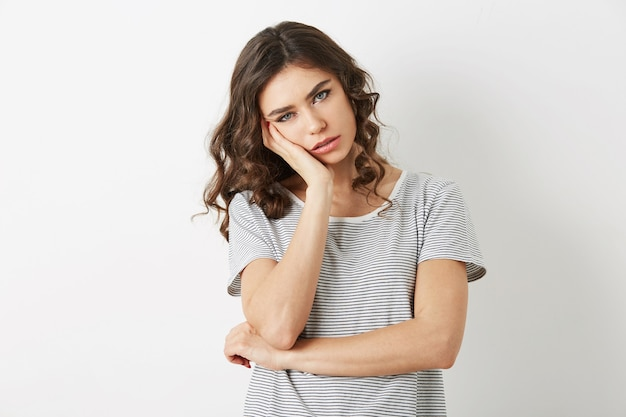 Ritratto di giovane signora stanca che ha un problema, frustrato, stress, triste emozione, isolato, guardando a porte chiuse, semplice t-shirt