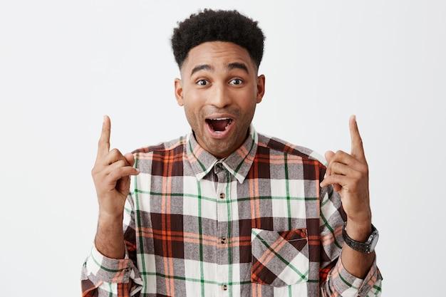 Ritratto di giovane sorpreso bello uomo dalla pelle nera con acconciatura afro in camicia a maniche lunghe casual rivolta verso l'alto con entrambe le mani con la bocca aperta e le sopracciglia sollevate.