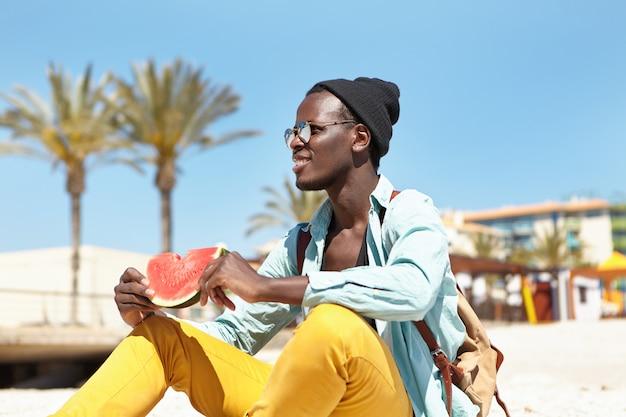 Ritratto di giovane spensierato dalla pelle scura in elegante copricapo e occhiali da sole rilassante sulla spiaggia con fetta di anguria fresca e succosa, ammirando il mare blu calmo durante le vacanze in località turistica