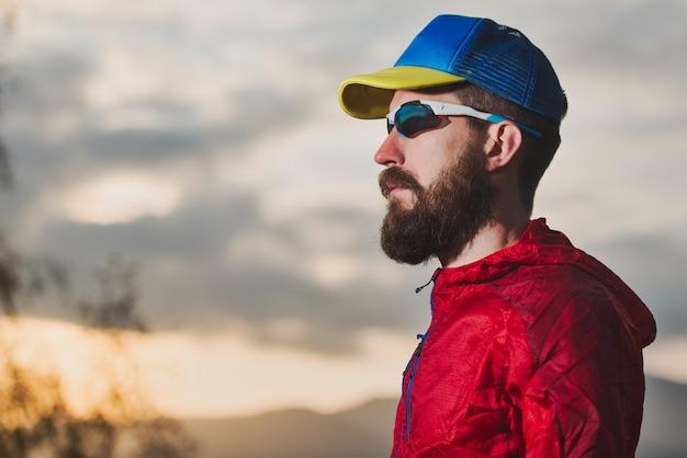 Ritratto di giovane sportivo con la barba durante il riposo in montagna