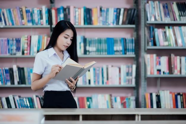 Ritratto di giovane studente che legge un libro in una biblioteca