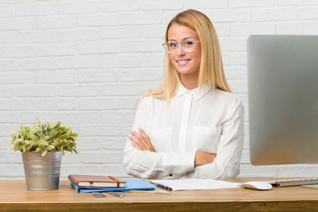 Ritratto di giovane studente seduto sulla sua scrivania facendo compiti che attraversano le braccia